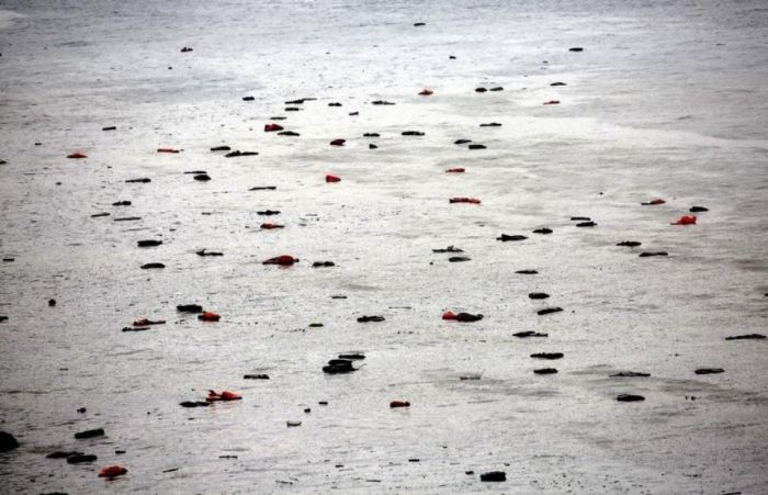 845321-life-vests-and-tubes-left-by-migrants-float-by-a-beach-during-a-rain-storm-on-the-greek-island-of-le